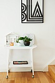 Retro side table on castors below framed geometric picture on white wall