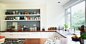 Shelves of crockery in grey-painted niche and U-shaped kitchen counter with wooden worksurface