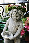 Stone statue wearing wreath of flowers as garden decoration