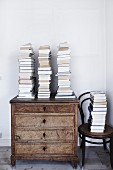 Stacked books on old chest of drawers next to Thonet chair