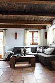 Rustic, wooden coffee table in front of comfortable corner couch in interior with wooden ceiling
