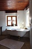 Free-standing bathtub below window in renovated bathroom