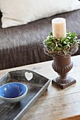 White candle in candlestick with wreath of flowers next to blue ceramic bowl on tray