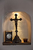 Crucifix and table clock in illuminated niche
