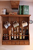 Stoneware beer mugs hanging above bottles on wooden, wall-mounted shelf unit