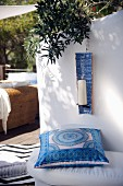 Blue and white patterned cushion on bench and candle in ceramic candle holder hung on wall of Mediterranean terrace