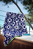 Weiss-blaues Ikatmuster auf Tuch, über Geländer gehängt