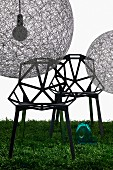 Spherical pendant lamps (Random Light) made from fibreglass mesh and designer chairs with hexagonal struts on lawn