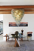 Foyer with opulent chandelier and round glass table top on wooden frame in front of bench and umbrella stand