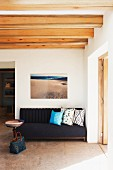 Picture of beach above sofa with scatter cushions, bowl on table and woven bag on floor