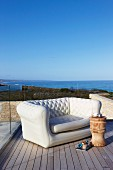 Elegant sofa and stool used as side table on wooden deck with sea view