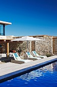 Sun loungers and parasol on wooden deck by blue pool in front of stone wall