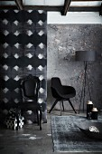Corner furnished in shades of grey and black; black, postmodern, upholstered chair and armchair in background next to standard lamp