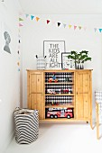 Toys on open-fronted shelves of wooden sideboard and black and white striped basket in corner of child's bedroom with colourful bunting on wall