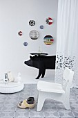 White chair and clogs on rug, black wild boar sculpture with tray table and colourful wall plates