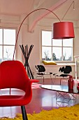 Classic design in loft apartment - red shell chair, arc lamp, elliptical table, cowhide chairs and coat stand