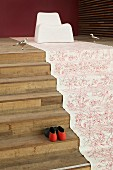Floral fabric runner laid on wooden steps and modern shell chair majestically arranged as throne flanked by silver bird figurines