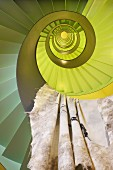 Deceptive view up lime green spiral stairwell with cloth hanging over balustrade