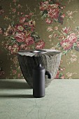 Two grey vases in front of elegant rose-patterned wallpaper