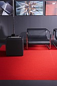 Dark grey lounge chairs, pouffe and wall enlivened by red carpet and gallery of artworks