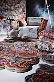 Artistically designed, colourful rugs, patterned cushions, and stylised teapot and teacup in front of armchair
