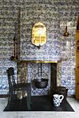 Kochtopf über der offenen Feuerstelle eines Kamins mit alten Delfter Fliesen, davor ein postmoderner Eisenstuhl mit Lochstruktur