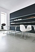 Purist tables, classic chairs and black wall with long, white, floating shelves