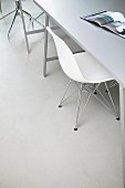White Eames shell chair at table and open magazine
