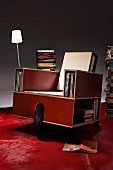 Multifunctional armchair made from laminated wood with large wheel, shelf openings for books and table lamp on red carpet