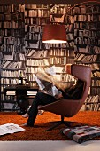 Woman reading in designer, leather easy chair below arc lamp in front of photo mural of bookcase