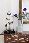 Ceramic vase and prepared butterflies under glass cover on marble mantelpiece