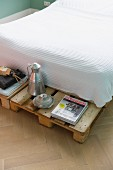 Bed with waffle piqué bedspread and protruding pallet frame used as bedside table