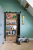 Sliding door with integrated shelves in child's attic bedroom