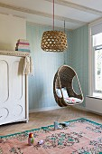 Wicker hanging basket and lampshades in child's bedroom