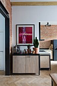 Open-plan, modern kitchen with wooden doors, black frames and modern artwork above collection of cacti
