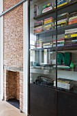 Fitted shelving with welded steel and glass doors next to fireplace in brick wall