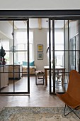 View through glass and steel sliding doors into open-plan kitchen with dining area