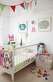 Cot, white wicker trunk, doll and toys in child's bedroom: children's clothing in picture frames on wall