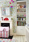 Shelves of soft toys and books in niche, floral wallpaper and pink dolls' house in front of disused fireplace