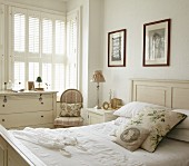 Traditional bedroom in vintage white with floral scatter cushions and floral pictures on wall above bed