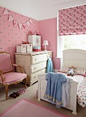 Girl's bedroom with pink patterned wallpaper and fabrics combined with white, country-house furnishings and antique armchair