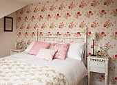 Double bed with white, metal, lattice frame in romantic bedroom with floral wallpaper