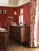 Sideboard with drawers in dining room with red-painted walls and floral curtains in English, country-house style