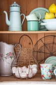 Enamel crocker, wire egg basket & other vintage kitchen equipment in dresser