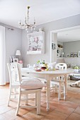 White kitchen chairs around dining table in pale grey dining room with tiled floor and chandelier