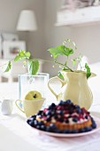Berry tart on plate in front of lemon balm in large jug and apple in small jug