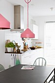 Pendant lamps with pink lampshades above black metal dining table; kitchen counter against white-tiled wall in background