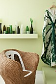 Rattan armchair in front of collection of green and white vases on white floating shelf
