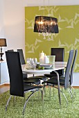 Pendant lamp with black fabric lampshade above chairs with black leather covers, oval dining table and rug; large artwork with bird motif on wall