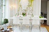 Chairs with white slotted backrests around dining table with vase of tulips in front of floral wall hanging